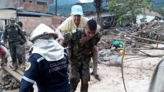 A woman is rescued from the landslide by a Colombian soldier