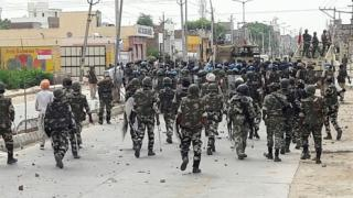 """Indian paramilitary personnel walk towards the """"Dera Sacha Sauda"""" Ashram in Sirsa on August 26, 2017, after followers of controversial guru Ram Rahim Singh on August 25 went on a rampage after their spiritual leader was convicted of rape."""