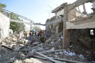 People stand on the rubble of a prison struck by Arab coalition warplanes in al-Zaydiyah district of the Red Sea port city of Hodeidah, Yemen October 30, 2016.