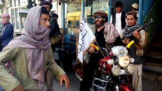 In this Sept. 29, 2015 file photo, a Taliban fighter sits on his motorcycle adorned with a Taliban flag on a street in Kunduz, Afghanistan