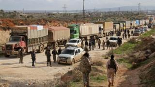 Fighters stand near a convoy of vehicles carrying UN food and medical aid on the outskirts of the rebel-besieged Kefraya. Photo: 14 March 2017