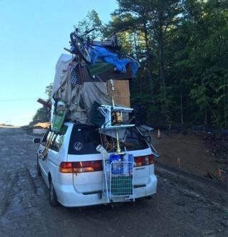 New Hampshire State Police post a photo of a van overloaded with household items including a table, a television and a shopping cart strapped to the outside of the vehicle.