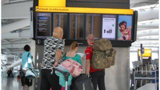 A family looks at a signboard in Heathrow Terminal 5