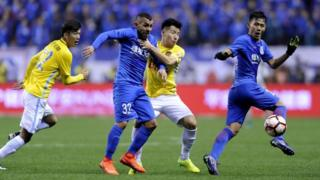 Shanghai Shenhua's Argentine striker Carlos Tevez (2L) fights for the ball with Yang Xiaotian (2R) of Jiangsu Suning during their Chinese Super League football match in Shanghai on March 5, 2017