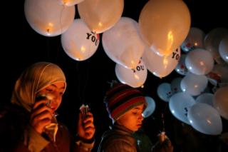 Children carry balloons before releasing them towards Damascus from the rebel-held suburb of Jobar, 30 December