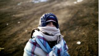 A migrant child wrapped in blankets tries to keep warm near the Macedonian-Serbian border