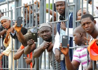 Liberians uses their mobile phones to take a photo of Sheikh Ahmed Mohammed Awal during his Dawah Tour at the Antoinette Tubman Soccer Stadium in Monrovia, Liberia on 9 July 2017