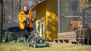 A Posti photo showing a female postal worker mowing a lawn