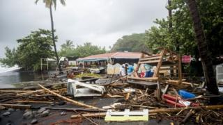People clear debris in Le Carbet, on the French Caribbean island of Martinique, after it was hit by Hurricane Maria.