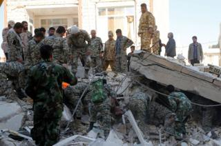 More than 20 soldiers around and under a slab of concrete in a pile of rubble