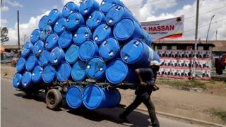 A porter transports a cart loaded with empty plastic drums to a recycling dealer
