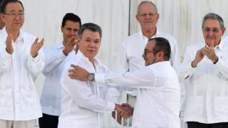 President Santos and Timochenko shaking hands after signing the deal