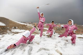 Students of the Shaolin Wushu club show their Wushu skills to other students on a hilltop in Kabul, Afghanistan.