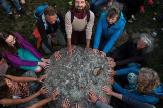 Revellers in a circle touch a stone at Stonehenge