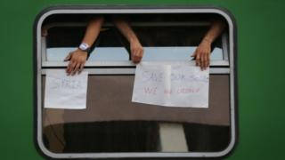 "People on train at Budapest Railway Station hold signs saying ""Save our souls"""