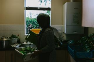 A participant holds a chopping board and bowl of vegetables in the kitchen