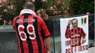 A supporter of the AC Milan football club wears a jersey of the honorary president of the club Silvio Berlusconi