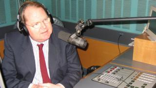 Mark Colvin sits in front of a radio microphone at the Australian Broadcasting Corp