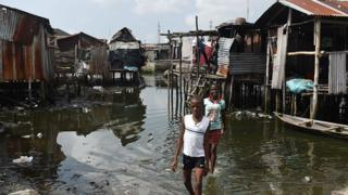 Children paddle in water in a Nigerian shanty town