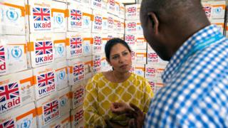 """Britain""""s International Development Secretary Priti Patel speaks with a humanitarian aid agency worker in front of boxes of food aid at Mogadishu airport, Somalia June 17, 2017."""