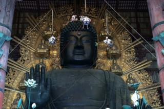 The Great Buddha of Nara at Todaiji Temple is cleaned by monks on pulleys.