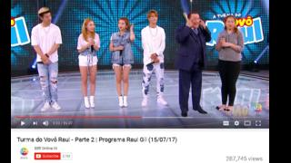 """A still from YouTube showing Brazilian TV host Raul Gil making a """"slant eye"""" gesture while interviewing Korean pop group KARD"""