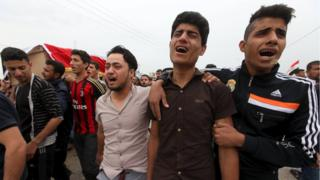 Mourners attend the funeral of a victim killed by a suicide bombing at a soccer field in Iskandariya