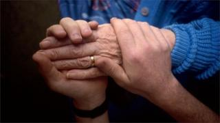Hands of carer and elderly woman