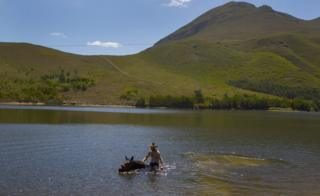 A man riding a horse in a dam in Greyton, South Africa - Saturday 25 February 2017