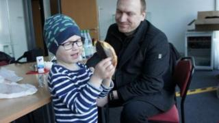 Andreas Graff smiles as he watches his son Julius play with a banana.
