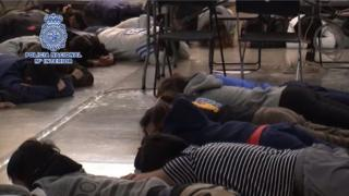 Taiwanese suspects lie on the ground during a police raid