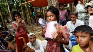 Rohingya children wait for their parents to receive aid at a distribution centre in Bangladesh