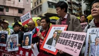 "Protesters hold up missing person notices of (L-R) Mighty Current publisher of books critical of China company""s general manager Lui Bo and colleagues Cheung Jiping, Gui Minhai, Lee Bo and Lam Wing-kei as they walk towards China""s Liaison Office in Hong Kong on January 3, 2016."