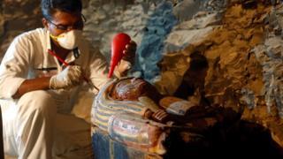 Археолог работает с находкой