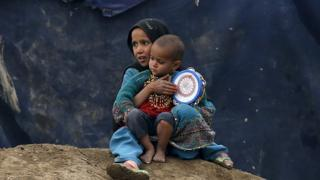 Internally displaced Afghan children sit outside their shelter in Kabul, Afghanistan
