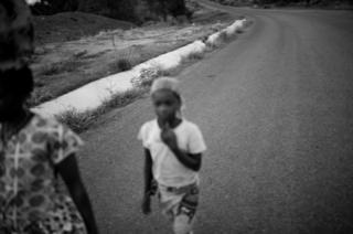 Elisa Piassone along with Zaida walk along the road between M'mele along with Kimar