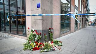 Flowers are pictured on April 8, 2017 at the site where a stolen truck was driven through a crowd and crashed into the Ahlens department store in central Stockholm the day before. The attack on Friday killed four people and injured 15, nine of them seriously