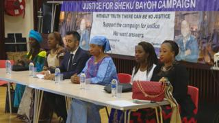Relatives of Sheku Bayoh sit in front of a banner with slogans campaigning for justice, after a memorial service in Kirkcaldy, Fife.