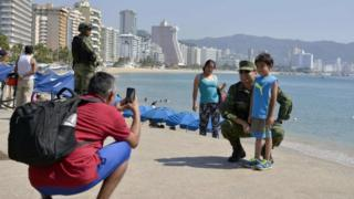 "A boy poses for a picture with a Mexican Army soldier patrolling along Acapulco""s coastline, in Guerrero state, Mexico on December 5, 2017."