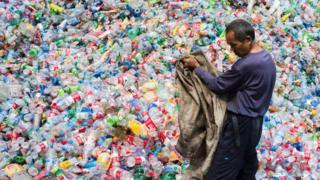 Chinese worker sorts through plastic bottles