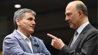 Greece's Finance Minister Euclid Tsakalotos (L) speaks with European Commissioner for Economic and Financial Affairs, Taxation and Customs Pierre Moscovici