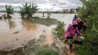 "Workers take a makeshift boat to cross flooded vegetable gardens in Madagascar""s capital Antananarivo, on Thursday, March 9, 2017"