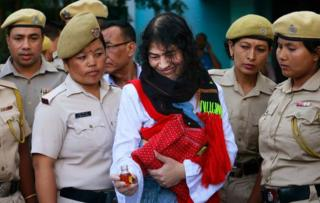 Indian political activist Irom Sharmila picks up a bottle of honey to break her fast in Imphal, north-eastern Indian state of Manipur, India, Tuesday, Aug. 9, 2016