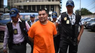 Former Guatemalan soldier Santos Lopez Alonzo escorted by Interpol agents after landing in Guatemala City, on August 10, 2016