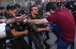 AFP haber ajansı geçtiği bu fotoğrafında sivil giyimli bir polisin LGBTİ aktivistine tekme attığını belirtti.