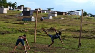 Crianças jogam futebol em cemitério em Rio Branco