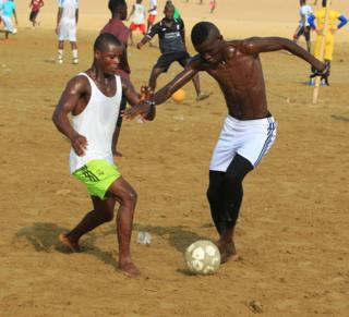 Young people on Sunday take to playing beach soccer in Monrovia, Liberia's capital
