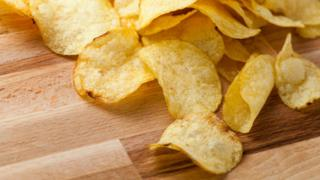 """A stock image of crisps (or """"potato chips"""" in some places) spilling across a wooden table."""