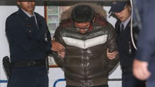 涉嫌性侵遊客的詹姓司機(中)被押離台北士林地方法院(台灣中央社圖片15/1/2017)