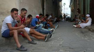 Personas conectándose a Internet a través de sus teléfonos celulares en La Habana.